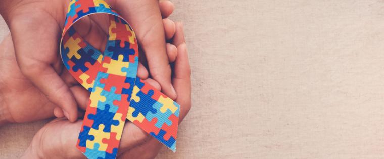 Mãos seguram um laço que é símbolo do autismo
